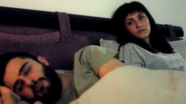 Žena v posteli při pohledu na spícího manžela