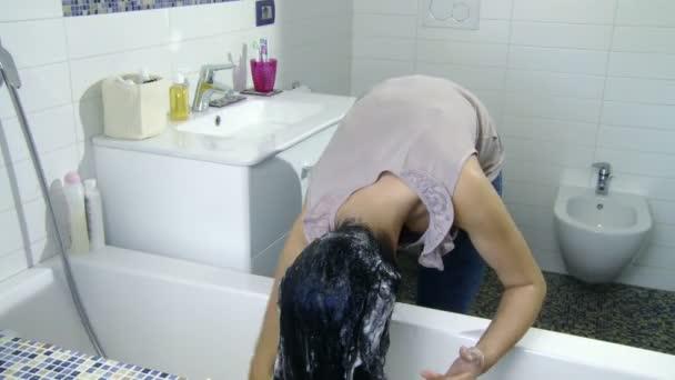 Frau, die ihren Kopf Shampoonieren