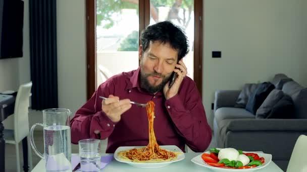 Geschäftsmann isst Pasta und telefoniert
