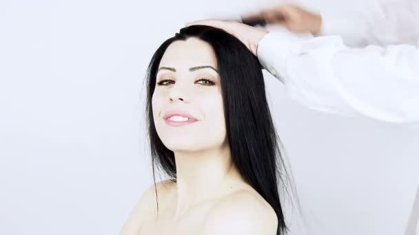 Friseur kämmt junge Frau die Haare