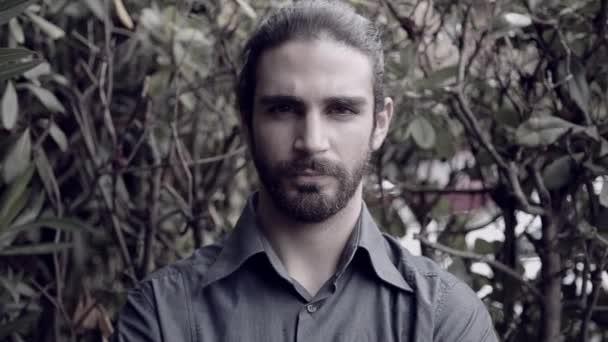 Hűvös jóképű férfi szakállal kamera keres