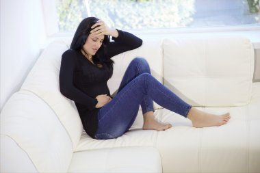 woman sitting on the couch at home with stomach ache
