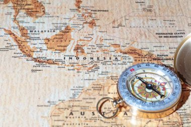 Travel destination Indonesia, ancient map with vintage compass