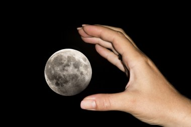 Hand catching the moon
