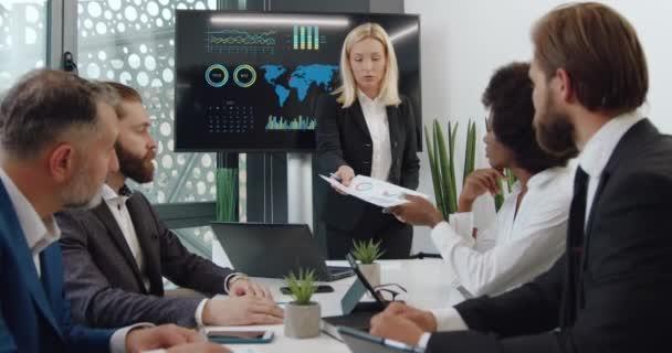 Attraktive, selbstbewusste, erfahrene blonde Geschäftsfrau, die ihren multiethnischen Geschäftspartnern während eines Treffens im Konferenzraum Finanzberichte mit Diagrammen übermittelt