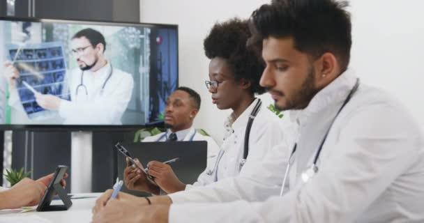 Atraktivní sebevědomí vysoce kvalifikované smíšené rasy lékařů pečlivě poslech on-line video prezentace v kanceláři