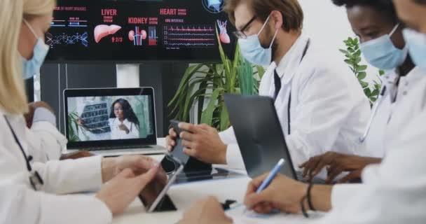 Attraktive konzentrierte erfahrene Mixed-Race-Mediziner in Masken sitzen am gemeinsamen Arbeitsplatz und beobachten Videokonferenz, Covid-19 Pandemie-Konzept