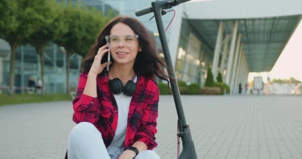 Porträt von entzückenden emotionalen Lächeln moderne stilvolle junge Brünette in lässiger Kleidung in Brille und mit Kopfhörern, die auf dem Smartphone sprechen, während sie auf ihrem eigenen E-Scooter in der Mitte der breiten