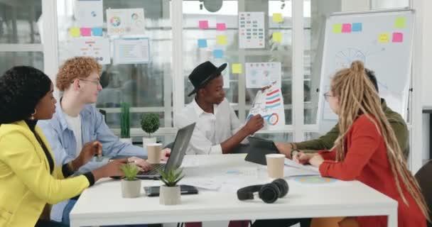 Attraktiver junger erfolgreicher Afroamerikaner erklärt seinen selbstbewussten, hochqualifizierten Mixed-Race-Kollegen beim Briefing im gläsernen Büroraum Infografiken