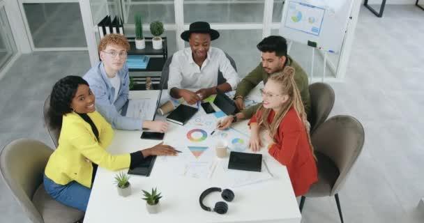 A jól kinéző, sikeres, képzett, nemzetközi kreatív férfiak és nők csoportjának áttekintése, akik együtt dolgoznak, és hüvelykujjal felfelé néznek a kamerába