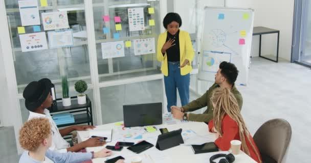 Draufsicht auf eine hübsch lächelnde emotional motivierte schwarzhäutige Frau, die mit ihrer konzentrierten kreativen Mischlingsrasse das Konzept der Geschäftsstrategie im Projekteinsatz unterordnet