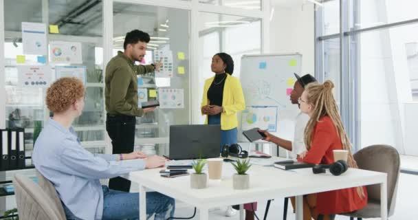 Detailní záběr dobře vypadající pozitivně motivované tvůrčí rozmanité skupiny, která pořádá setkání v kancelářské místnosti a diskutuje o různých zprávách s grafy