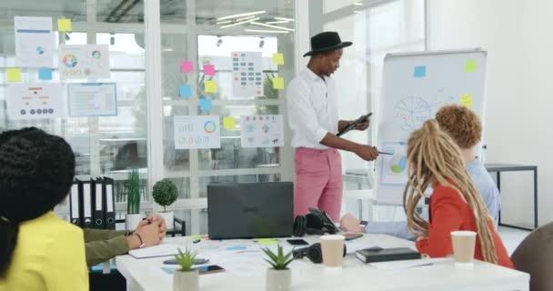 Detailní záběr dobře vypadajícího stylového zkušeného černošského pracovníka, který vysvětluje diagramy svým mužským a ženským smíšeným rasovým kolegům při setkání v zasedací místnosti