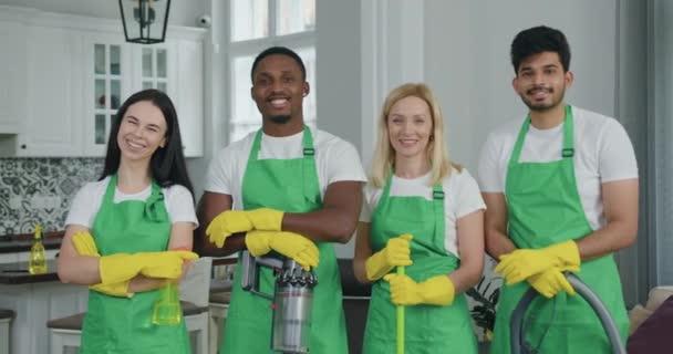 Porträt eines sympathischen, gut gelaunten, selbstbewussten Mixed Race Reinigungsteams in Spezialuniform, das mit erhobenem Daumen in der Kundenwohnung posiert