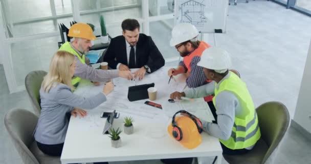 Top view vonzó szakképzett, sokszínű csapat mérnökök és szakállas főnök, akik ötletelés együtt tervrajzok építési során találkozó során a tanácsteremben