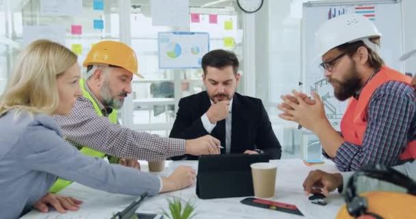 Atraktivní pozitivní sebevědomý kvalifikovaný mužský a ženský tým inženýrů nebo specialistů stavebního průmyslu při pohledu do kamery při setkání v zasedací místnosti