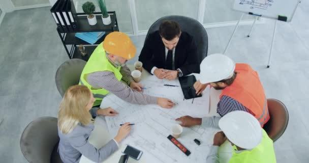 Top view szerethető magabiztos szakmai változatos csapat mérnökök mellény és keménykalap, amely ötletbörze a férfi és női vezetők építési projekt tárgyalóteremben