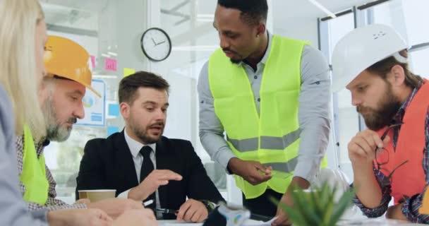 Gut aussehender, selbstbewusster, schwarzhäutiger Ingenieur, der seinem ernst zu nehmenden, hochqualifizierten, bärtigen Manager bei einem Treffen mit anderen Mitgliedern des Arbeitsteams Baudetails auf dem Bauplan erklärt