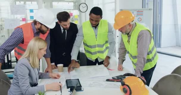 Atraktivní sebevědomý profesionální multiraciální tým inženýrů stavební společnosti, kteří analyzují stavební výkres se svým úspěšným vysoce kvalifikovaným vousatým ředitelem během setkání v zasedací místnosti