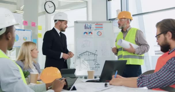 Attractive confident stylish bearded ceo or main manager of building company holding a meeting with professional skilled multiracial team of specialists-builders about building project