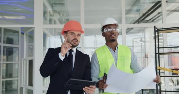 Portrét pohledného sebevědomého vousatého hlavního manažera v hardhat chůze s profesionálním africkým americkým inženýrem nebo stavitelem v přilbě, ochranných brýlích a vestě v nedokončené kancelářské budově a