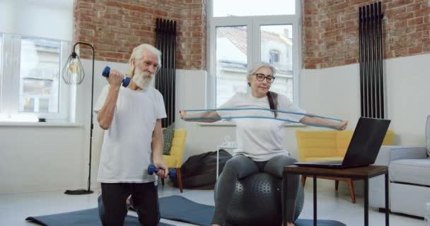 Schönes lächelndes, sportliches Senioren-Paar, das beim gemeinsamen Training zu Hause Sport mit Kurzhanteln und Stretchband macht, aus nächster Nähe