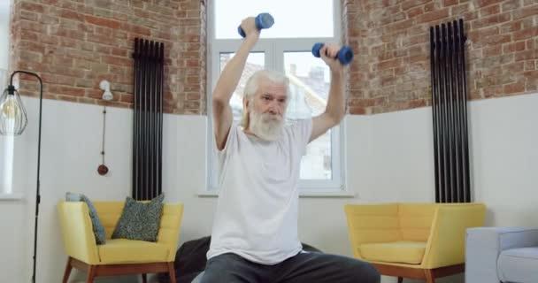 Vorderansicht des sympathischen, konzentrierten, bärtigen Seniors in Sportuniform, der auf Fitball sitzt und zu Hause Übungen mit Hanteln macht