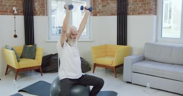 Attraktiver sportlich reifer bärtiger Mann in Sportbekleidung, der auf Fitball sitzt und beim Heimtraining Übungen mit Kurzhanteln macht, Zeitlupe