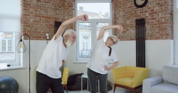 Porträt eines gut aussehenden, sportlich lächelnden Rentnerehepaares in Sportkleidung, das beim morgendlichen gemeinsamen Training von links nach rechts kippt