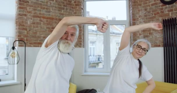 Likable joyful sportive healthy senior couple in sportswear doing stretching exercises with tilts left to right and looking at camera during joint workout at home