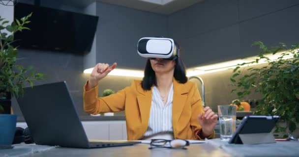 Attraktive, hochqualifizierte, seriöse Geschäftsfrau im Alter von 35 Jahren sitzt in stylischer Kleidung im Home Office in der Küche und arbeitet mit Augmented-Reality-Brillen am imaginären Bildschirm