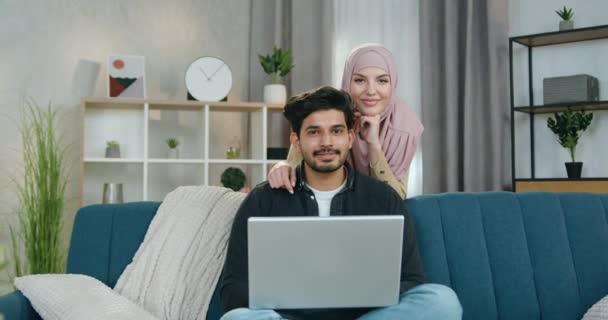 Familienporträtkonzept, bei dem ein gutaussehender lächelnder, glücklicher bärtiger Mann auf dem Sofa sitzt, seine charmante, fröhliche Frau im Hijab hinter ihm steht, während sie zu Hause gemeinsam vor der Kamera posieren