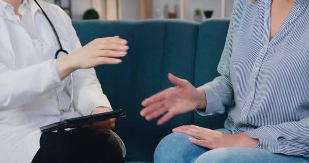 Neznámá zkušená a sebevědomá lékařka sedící se svou pacientkou na gauči a potřásající si rukou při návštěvě domova, konceptu zdravotní péče a medicíny