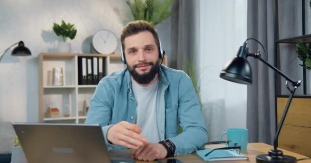 Portrét dobře vypadající usmívající šťastný přátelský mladý vousatý chlap ve sluchátkách, který pózuje do fotoaparátu tvorby znamení ok sedí na svém pracovišti doma
