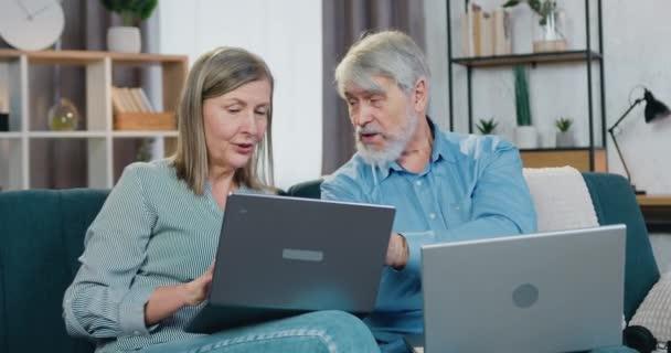Starší pár odpočívající na pohodlném gauči s osobními notebooky