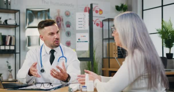 Konzentrierte Ärztin im Arztkittel sitzt am Tisch und berät Patientin mittleren Alters über Krankheit oder Operation