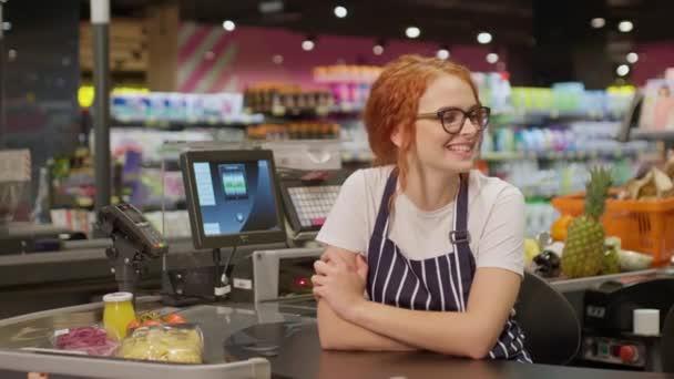 Elég vidám vörös pénztáros szemüvegben és csíkos kötényben boldogan pózol a kamera előtt, miközben a modern szupermarketben pénztárgép mögött dolgozik. Az élelmiszerbolt koncepciója