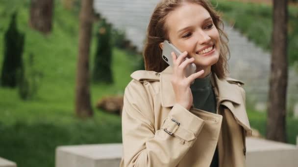 Porträt eines hübschen Studentenmädchens, das sich mit einem Freund auf dem Smartphone unterhält und im Freien lächelt