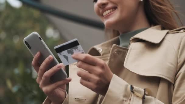 Közelkép mosolygós diák lány fizet az online vásárlások hitelkártyával okostelefon kültéri