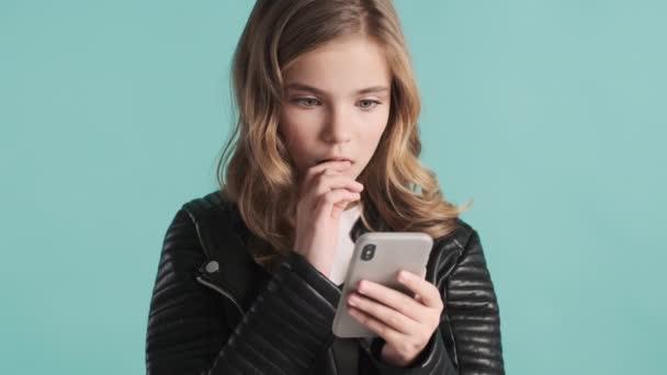Hübsches blondes Teenager-Mädchen, das eine Nachricht von einem Freund auf dem Smartphone bekommt und überrascht über den blauen Hintergrund schaut. Modernes Technologiekonzept