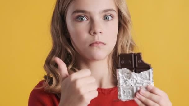 Nahaufnahme erstaunt blonde Teenager Mädchen essen köstliche Schokoriegel halten Daumen nach oben in die Kamera über gelbem Hintergrund. Wow-Gesicht. Gefällt mir.