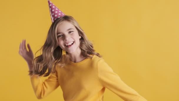 Beautiful excited blond teenage girl wearing birthday hat looking happy dancing on camera during birthday party over yellow background. Positive teen girl