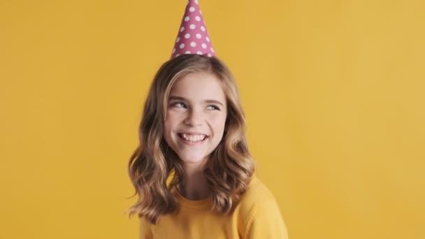 Hezké blond dospívající dívka na sobě party klobouk slaví své narozeniny s přáteli, kteří vypadají šťastně přes žluté pozadí. Narozeninová dívka