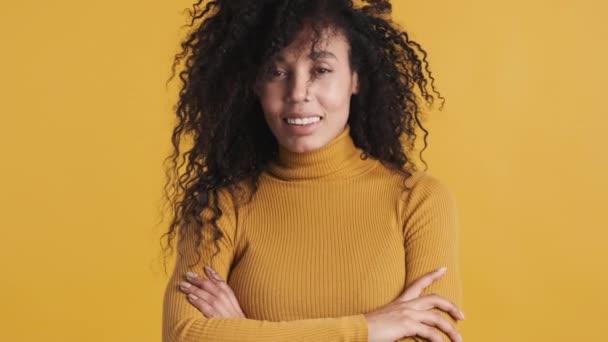 Fiatal gyönyörű afro-amerikai nő integetett fejét mutatja a kamera sötét bolyhos haj elszigetelt narancs háttér