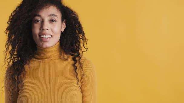 Vonzó Afro nő sötét göndör haj áll közel másolás helyet a reklám és mosolyogva sárga háttér. A szöveg helye