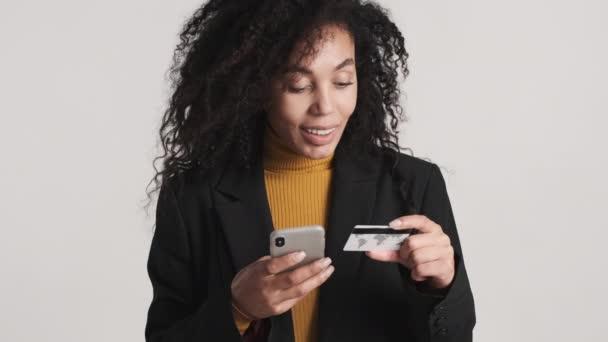 Schöne Afroamerikanerin stilvolle Frau, die für Online-Einkäufe per Kreditkarte bezahlen mit dem Smartphone dafür isoliert auf weißem Hintergrund. Moderne Technik