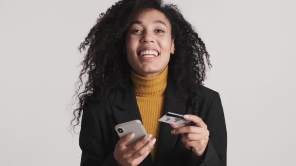 Junge Afroamerikanerin bezahlt Online-Einkäufe per Kreditkarte mit dem Smartphone und jubelt vor laufender Kamera vor weißem Hintergrund. Moderne Technik