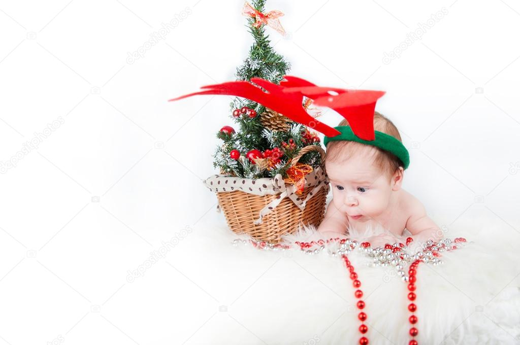 Nettes Baby mit lustigen Hirsch Geweih liegend auf dem Teppich in ...