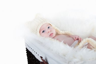 A cute little baby is looking into the camera and is wearing a white hat. The baby could be a boy or girl and has blue eyes.