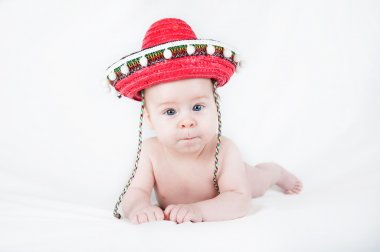 Cheerful little boy with a sombrero and maracas on a white background
